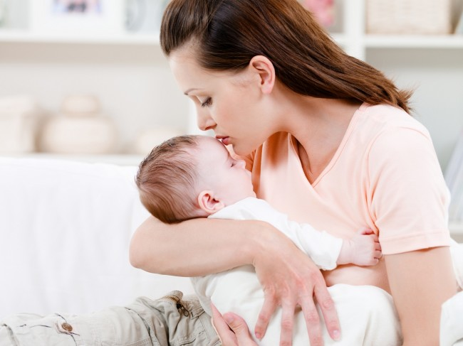 Мама проверяет температуру грудничка