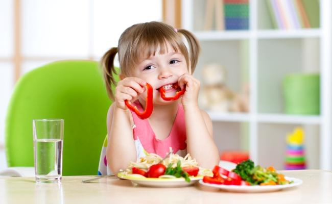 Девочка ест перец
