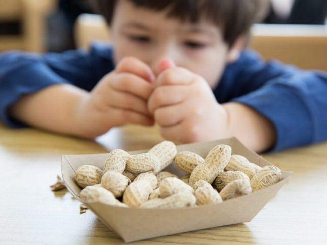 Мальчик чистит арахис