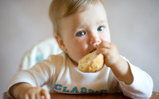 маленький ребенок ест хлеб