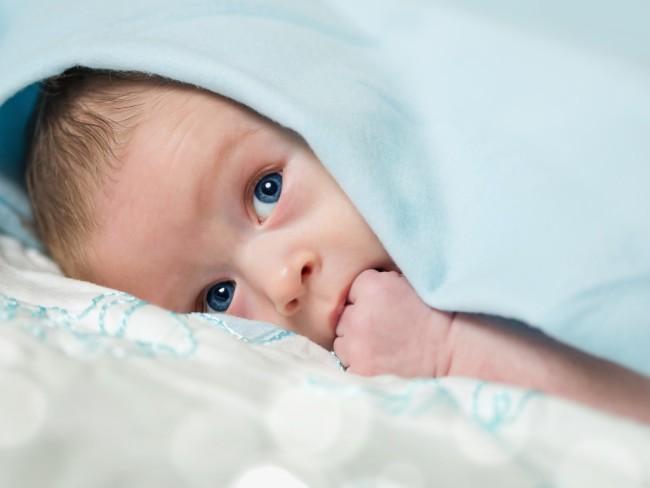 малыш с кулачком во рту